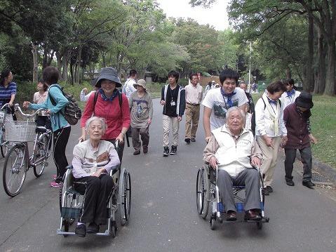 笑顔で車椅子を押す会員