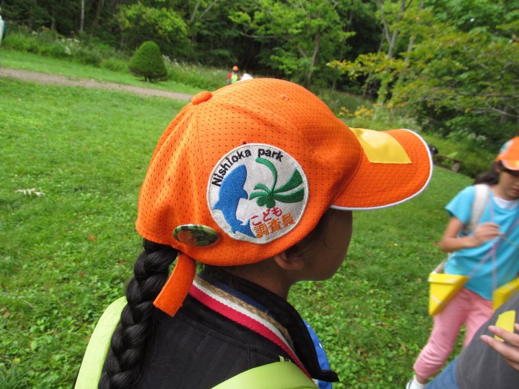 オレンジ色の帽子に「こども調査員」のワッペンがついています