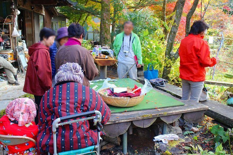 綾野さんから、かかしの作り方をきいている観光客。左手前に座っているのはかかしのおばあちゃんと孫