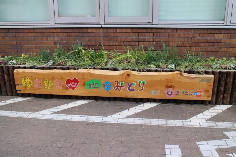 伐採した街路樹を再利用して地元小学生が「ゆたかな心 地にみどり」の標語を書いた表示板(江戸川区庁舎前)