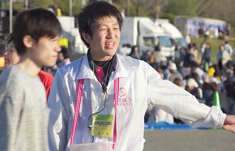 白いスタッフジャンパーを着て場内整備をする市民ボランティア