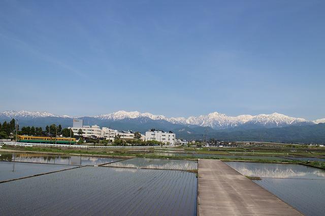 立山連峰を背景に、富山地方鉄道本線の電車が走る。昼間でも1時間に3~4本走っており、富山市内へのアクセスが良い。