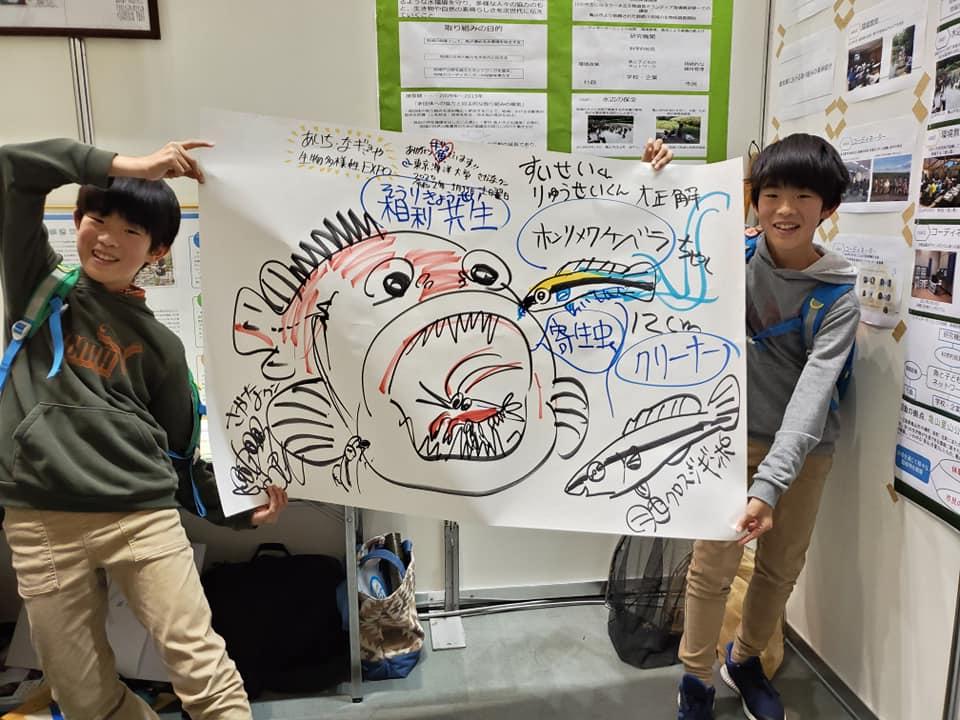 「あいち・なごや生物多様性EXPO」で講演した<br>魚類学者でタレントのさかなクンに<br>直筆の絵を描いてもらったKidsクラブメンバー<br>(<ruby>角崎瑠星<rt>かくざきりゅうせい</rt></ruby>くん、<ruby>翠星<rt>すいせい</rt></ruby>くん )