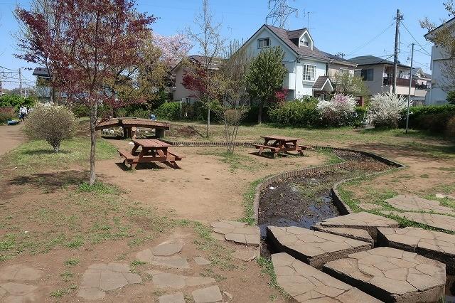 ワークショップで植樹した樹木と、みんなでつくったベンチの脇を井戸からの水が流れる