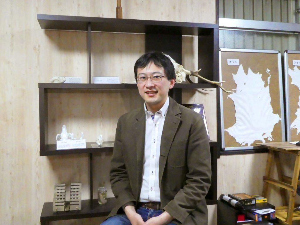 羽村太雅さん<br/>(バックは、「手作り科学館 Exedra」の<br/>動物の骨・革などが展示されている一角)